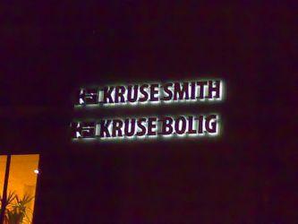 Fasadeskilt Kruse Smith med lys mot veggen dvs. profil 3.